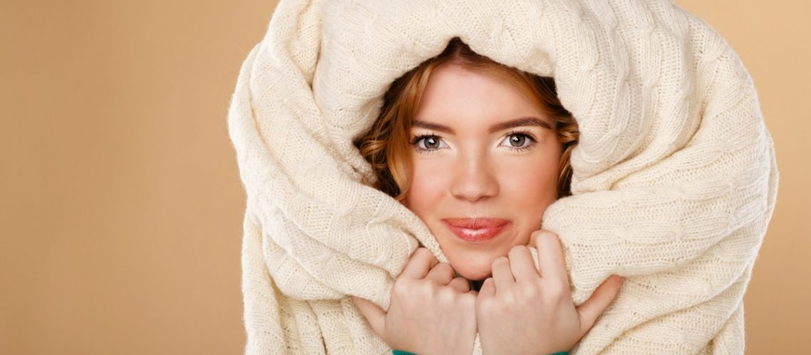 Beautiful young girl with curly hair wrapped in a warm blanket. The cold season. Home comfort.